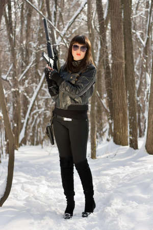 Pretty young woman with a pistol holster and rifle photo