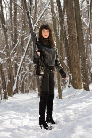 Dangerous hot lady with a rifle in forest photo