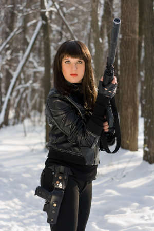 Portrait of dangerous lady with a rifle in forest