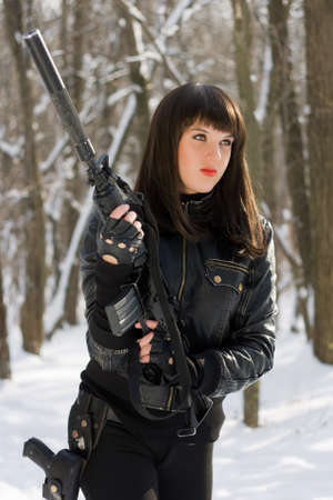 the silencer: Portrait of dangerous young lady with a rifle in forest Stock Photo