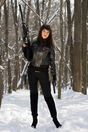 the silencer: Sexy young woman with a rifle in forest