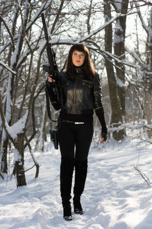 Gorgeous young woman with a rifle in winter forest photo