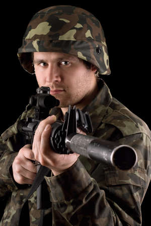 Watchful soldier aiming  m16 in studio. Isolated photo