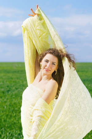 Portrait of a happy young woman wrapped in yellow cloth photo