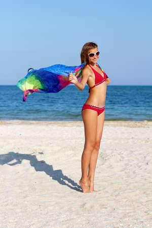 Cheerful teen girl standing on the beach with pareo in hands photo