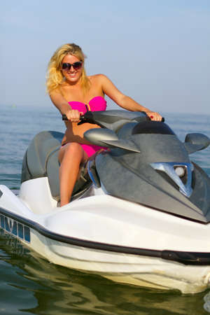 Beautiful smiling young woman on a jet ski