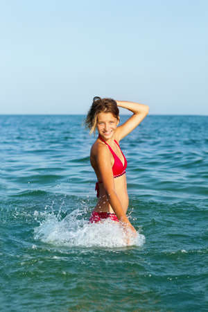 Cheerful teen girl having fun in the sea photo