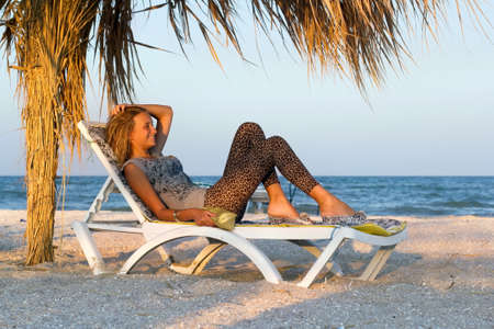 Smiling teen girl lying on a lounge chair photo