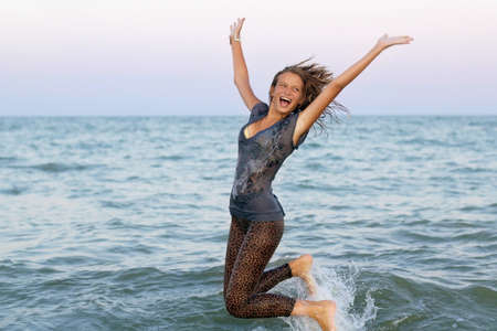 Cheerful wet teen girl having fun in the sea photo