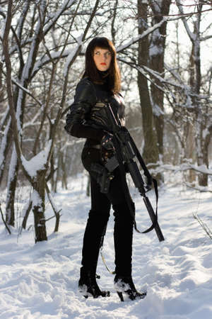 Armed beautiful young lady in winter forest photo