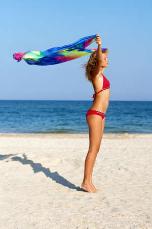 Dreamy teen girl standing on the beach with pareo in hands photo