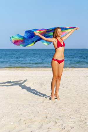 Dreamy cute teen girl standing on the beach with pareo in hands photo