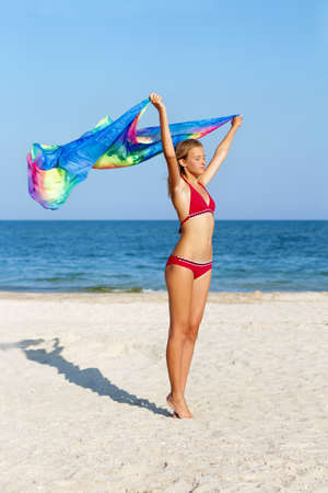 Dreamy lovely teen girl standing on the beach with pareo in hands photo