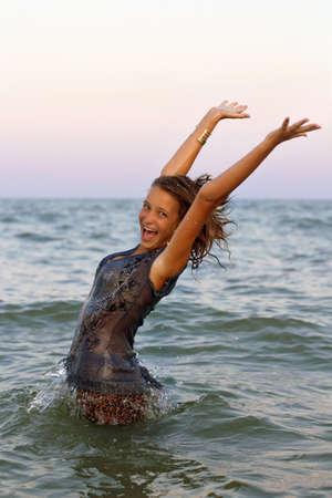 Happy wet teen girl having fun in the sea photo