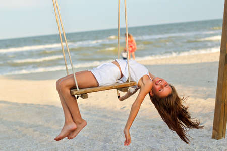 Funny cheerful little girl swinging on a swing photo