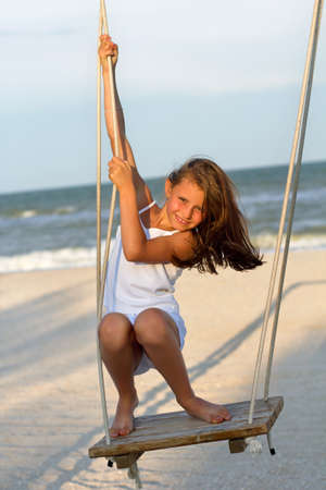 Cheerful little girl swinging on a swing photo
