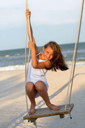 Cheerful little girl swinging on a swing