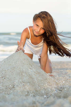 Pretty little girl playing on the beach
