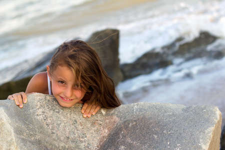Pretty playful little girl on the beach photo