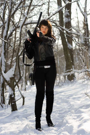 M16: Armed beautiful young woman in winter forest Stock Photo