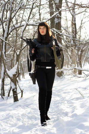 Armed gorgeous young lady in winter forest photo