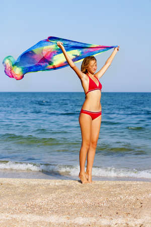 Lovely teen girl standing on the beach with pareo in hands