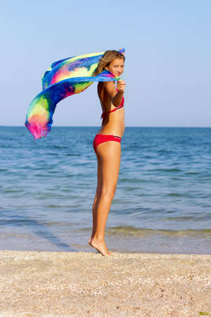 Attractive teen girl standing on the beach with pareo in hands photo