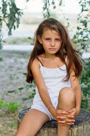 klein meisje op strand: Mooi meisje zittend op een boomstronk Stockfoto