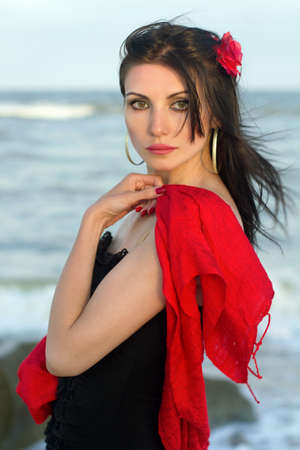 Portrait of young brunette in black dress on the beach Stock Photo