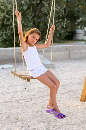 Pretty little girl swinging on a swing outdoors