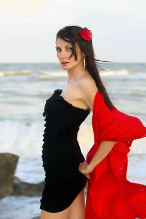 Portrait of pretty young brunette in black dress on the beach photo