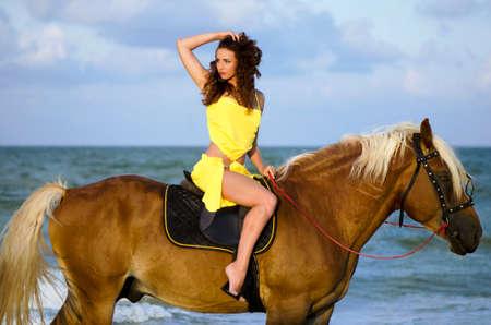 caballo de mar: Mujer joven que monta un caballo en la playa Foto de archivo