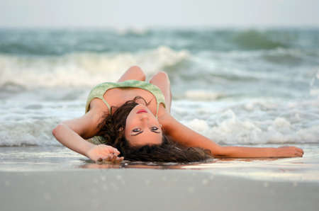 Attractive young woman lying on the beach photo
