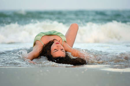 Pretty young woman lying on the beach photo