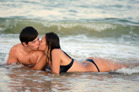 Young couple kissing while lying in waves photo