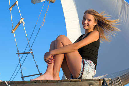 Beautiful teen girl sitting at stern of the ship photo