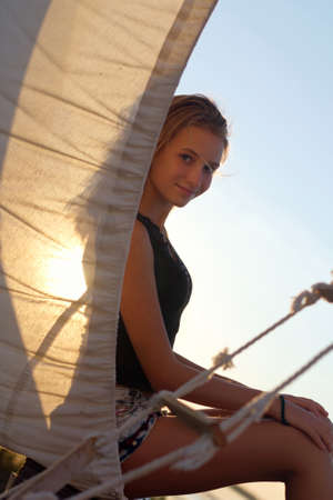 Charming teen girl sitting at stern of the ship Stock Photo