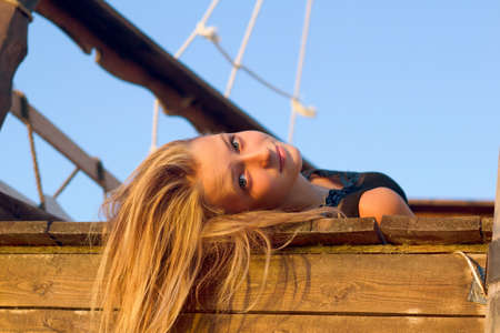 Pretty girl lying on the deck of an old wooden ship Stock Photo - 16720937
