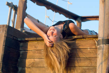 Joyful girl lying on the deck of an old wooden ship