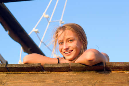 Smiling girl lying on the deck of an old wooden ship Stock Photo - 16797044