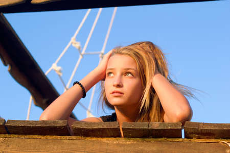 Dreamy girl lying on the deck of an old wooden ship Stock Photo - 16797038