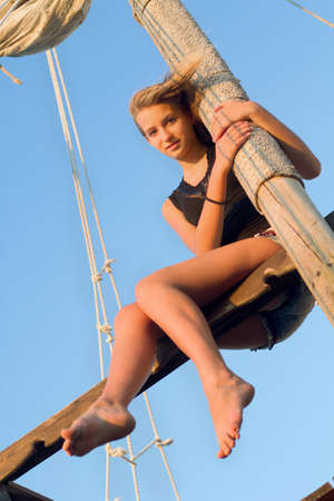 Teen girl hugging the mast of an old wooden ship photo