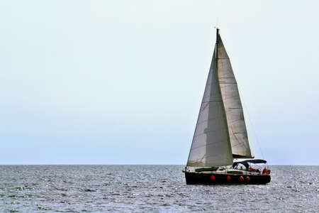 Small sailing yacht on the sea waves photo