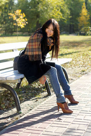 Happy young woman sitting on a bench in autumn park photo