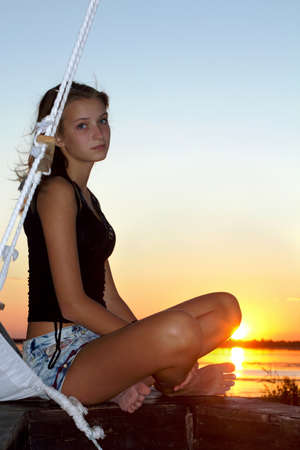 mast: Beautiful teen girl sitting at stern of the ship