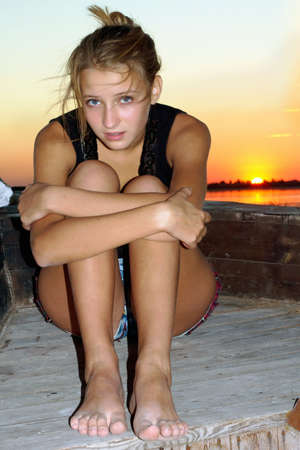 Upset teen girl sitting at stern of the ship photo
