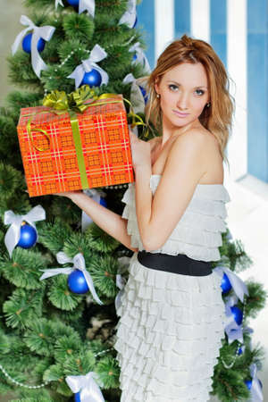 Young woman with a Christmas present in the orange box Stock Photo - 16921532