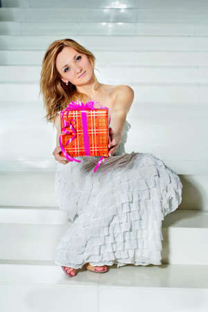 Attractive young woman with a present sitting on the stairs photo