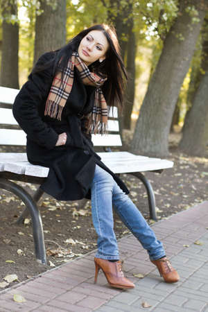 Cute young woman sitting on a bench in autumn park photo