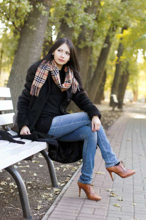 Perfect young woman sitting on a bench in autumn park photo